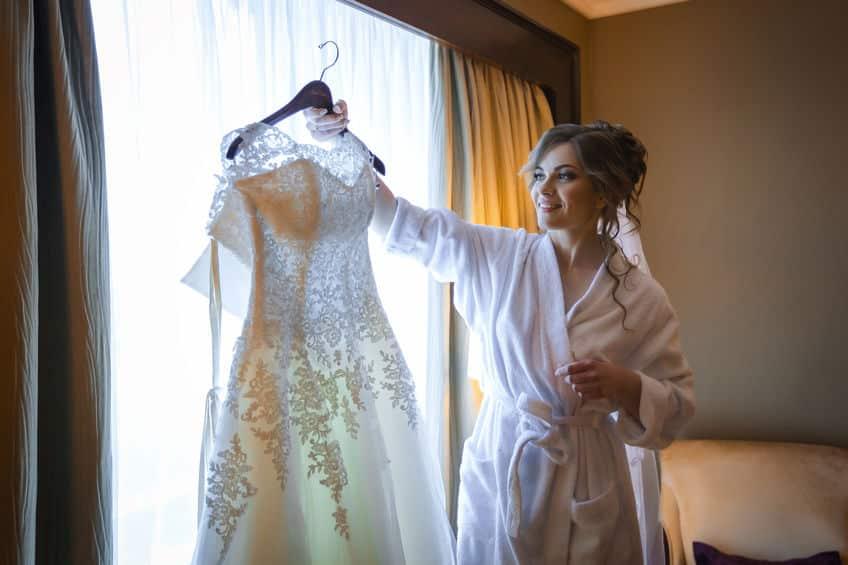 Noiva olhando para o vestido no making off