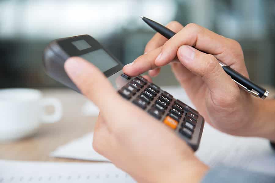 Pessoa fazendo contas com uma calculadora, com dicas de gestão para fotógrafos.