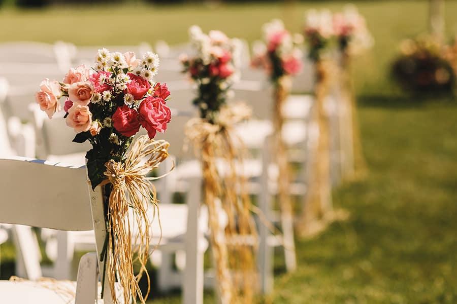 Fotografia dos detalhes de um casamento, com pequenos buquês de flores enfeitando as pontas das cadeiras dos convidados.