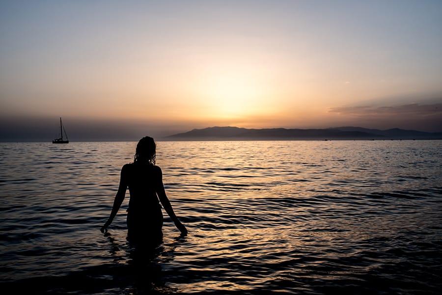Fotografia com silhueta de uma mulher na praia